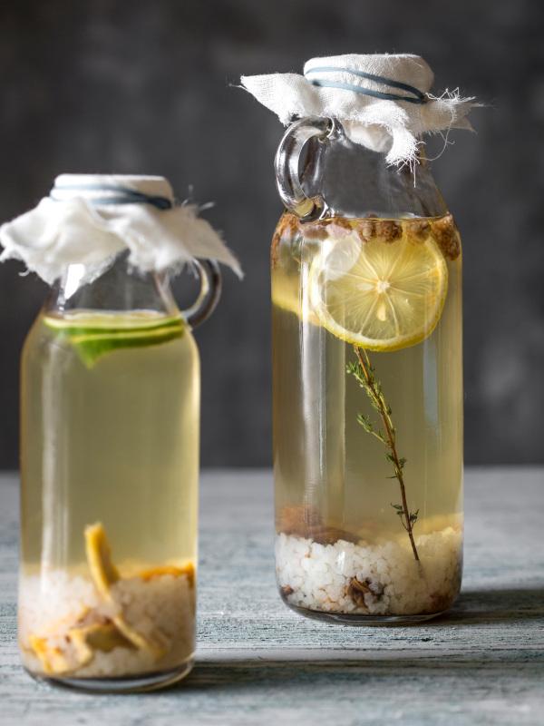 Water Kefir in bottles with grains herbs and lemon