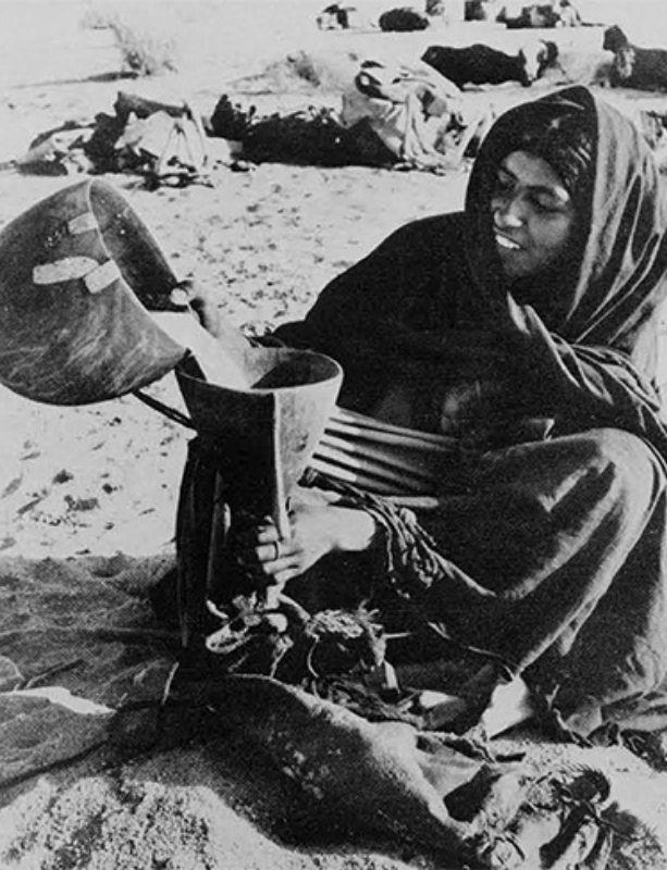 Femme nomade en train de verser du lait dans une outre en peau de chèvre