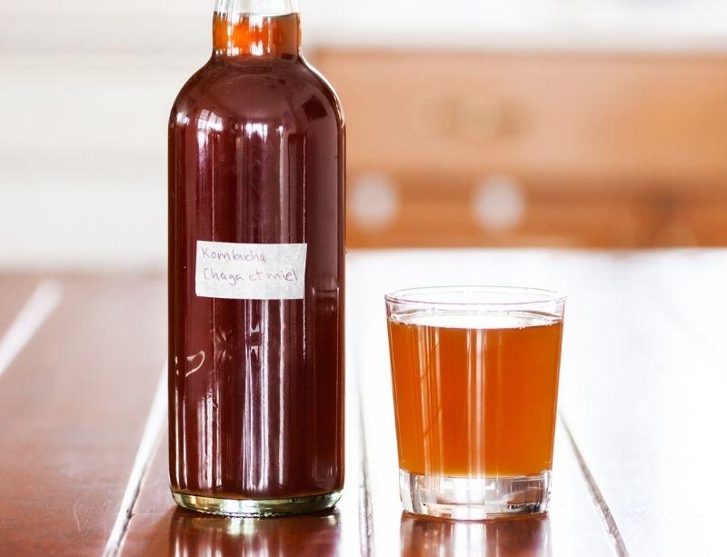 Verre et bouteille de kombucha au chaga et au miel